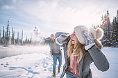 Playful couple snowball fighting in winter
