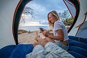 Young couple inside tent using mobile phone, two people camping on the beach