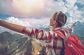 Woman on top of the mountain standing arms outstretched