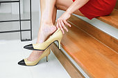 Businesswoman wearing high heels shoes after work at home.