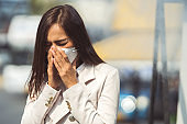 Asian woman are going to work.she wears N95 mask.prevent PM2.5 dust and smog.she is coughing