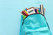 education and back to school concept. stationery in the mint bag over blue wooden background. top view, flat lay