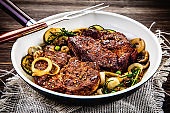 Grilled pork steaks and vegetables on frying pan