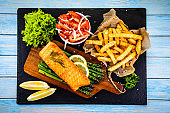 Grilled salmon with French fries and vegetables on wooden table
