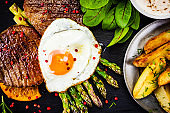 Grilled steak with sunny side up egg, fried potatoes and vegetable salad