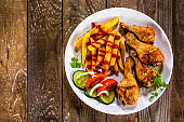Roast chicken legs with french fries and vegetables