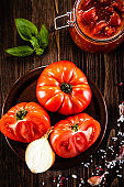 Raw tomatoes and tomato sauce  on wooden background