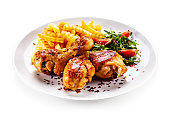 Roast chicken drumsticks with french fries and vegetables