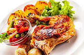 Roast chicken drumsticks with fried potatoes and vegetables