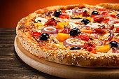 Pizza margherita with ham and pepper on wooden background