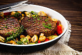 Grilled beef steak and vegetables in pan