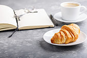 Morning cup of coffee and croissant for breakfast. Day planning, empty notebook, pen and glasses on gray table.