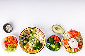 Buddha bowls on white background. Colorful bowls with vegetables, healthy grains, and protein.
