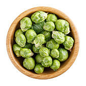 Fresh raw organic brussels sprouts in wooden bowl isolated on white. Top view, close-up.