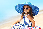 Summer holidays, vacation concept - portrait beautiful little girl in straw hat, striped dress relaxing on beach near sea
