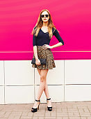 Fashionable young blonde woman model in leopard skirt, sunglasses with handbag clutch posing on city street over colorful pink wall background