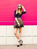Fashionable young blonde woman in leopard skirt, sunglasses with handbag clutch posing on city street over colorful pink wall background