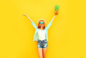 Happy smiling young woman raises her hands up with pineapple having fun in summer straw hat, sunglasses, shorts on colorful yellow background