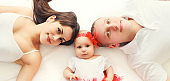 Portrait close-up happy family mother, father with baby lying on bed or carpet at home, top view