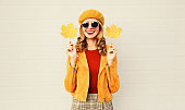 Autumn mood! Stylish happy smiling woman with yellow maple leaves in french beret over gray wall background