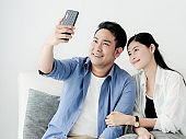 Happy honeymoon couple making video call to their family for lifestyle concept.