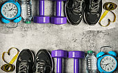 Sport shoes, blue alarm clock, bottle of water and centimeter on grunge cement background background. Sport equipment. Concept healthy life.