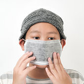 Asian preteen boy wearing earloop  carbon mask on white background.