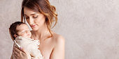 Pretty young woman holding a newborn baby in her arms. Portrait of mother and little baby. Happy family concept. Copy space