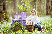 Little girl  play with real rabbit in the garden. Laughing child at Easter egg hunt with  pet bunny. Spring outdoor fun for kids with pets