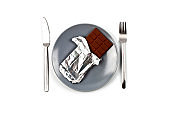 Chocolate bar with foil on grey ceramic plate, fork and knife on white background.