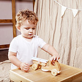 Child boy playing in his room with a wooden toy car