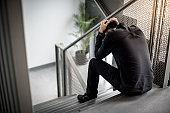 Asian man feeling stressed sitting on stair