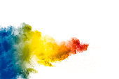 Colorful powder explosion on white background. Abstract pastel color dust particles splash.