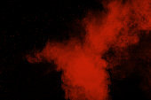 Red color powder explosion on black background.Freeze motion of red dust particles splashing.