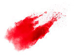 Abstract red dust splattered on white background. Red powder explosion.Freeze motion of red particles splashing.