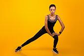 Afro Girl Doing Side Lunge Exercise Stertching Leg, Studio Shot