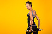 Determined Afro Girl Working Out With Dumbbells On Yellow Background