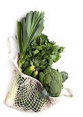 Mesh shopping bag with green healthy and organic vegetables