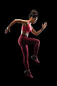 Afro fitness girl jumping over black background