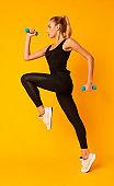 Fitness Girl Jumping Holding Dumbbells Over Yellow Background, Studio Shot