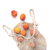 Organic peaches in eco string shopping bag on white