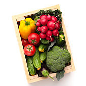 Fresh and organic vegetables in wooden box on white