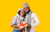 Smiling black couple carrying big xmas gift