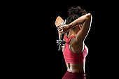 Black athletic girl working on her back muscles, using barbell
