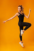 Fit Lady Jumping During Workout Over Yellow Background