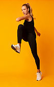 Sporty Woman Jumping Exercising In Studio Over Yellow Background