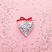 Heart of white paper with red bow on pink background