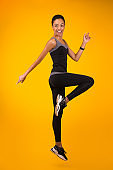 African American Girl Exercising Jumping Over Yellow Background, Full Length