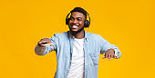 Black guy dancing while listening his favorite music in headphones