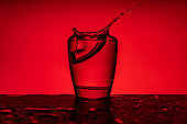 Aspirin paracetamol pill splashing into glass of water - red  background